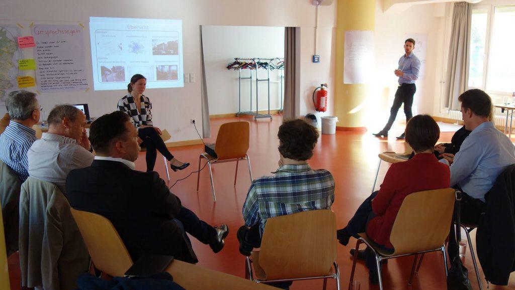 Dargestellt ist die Durchführung einer Fokusgruppe für die Mobilitätsberichterstattung in Berlin-Pankow, bei der die Teilnehmenden im Halbkreis um die Moderation sitzen und gemeinsam über Themen der Mobilität diskutieren.